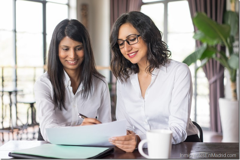 Two smiling female coworkers planning in cafe