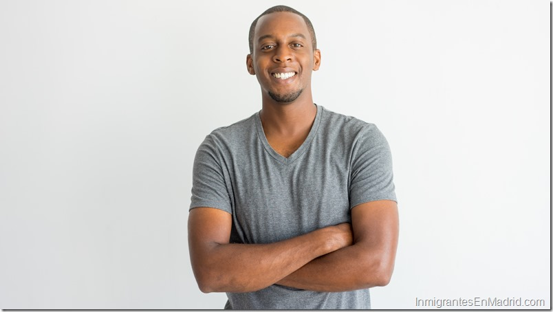 Happy excited young African man crossing arms on chest