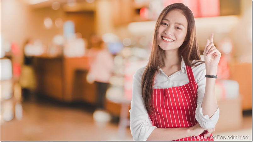 Portrait of Smiling beautiful young Asian woman wear red apron and hand pointing with copy space for your text or advertising isolated on white.