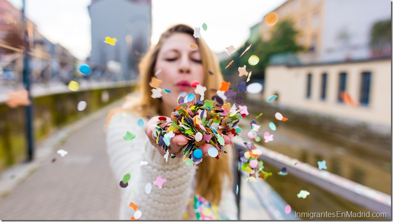 CLose up on the hand of a caucasian blonde woman blowing carnival confetti hand hold - canrival, party, colorful concept