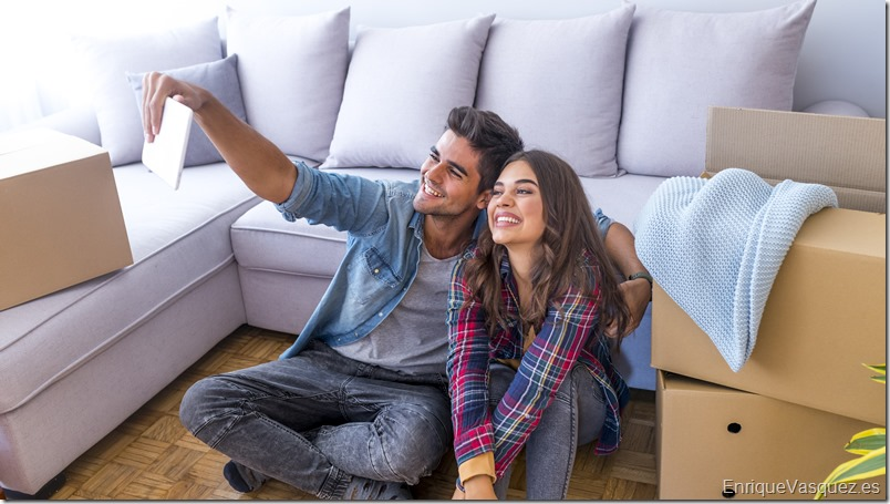 Cheerful and happy young couple making a selfie in new home with moving cardboard box during move into new apartment