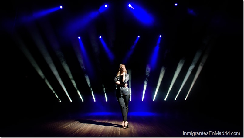 pretty woman artist over the background of blurred spotlights on the stage